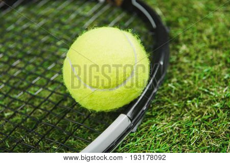 Close-up View Of Tennis Racquet And Ball On Green Grass