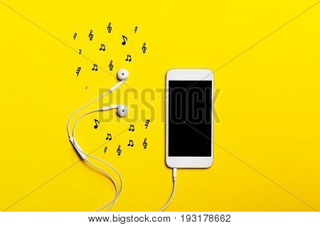 Close-up of smart phone with headphones on a yellow background. Listen to music.