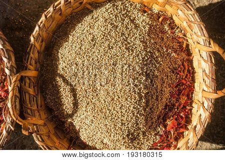 A wicker basket with many fried whole coriander seeds and chili peppers. Preparation for the feast in a Hindu temple