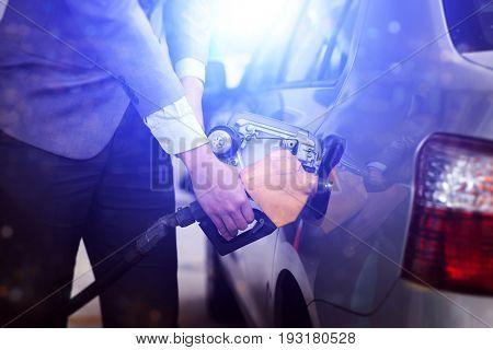 Refilling gas. Close up of man pumping petrol in car at petrol station.