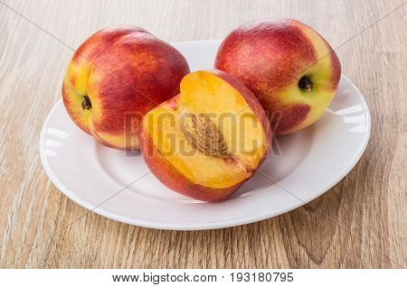 Two Full Nectarines And Cut Nectarine In White Plate
