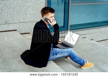 Portrait of young man sitting on stairs outdoors with laptop computer and talking on cell phone. Laptop computer with white blanck display screen