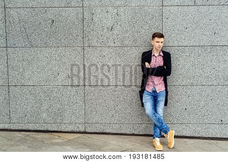 Handsome casual young man in plaid shirt and jacket posing near stone wall outdoors free space. Teenager with crossed hands. Full body length portrait fashion and people concept