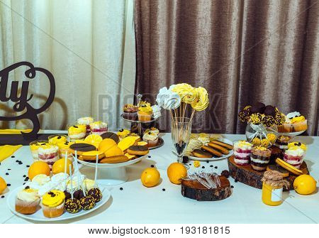 Holiday candy bar in yellow and brown color. Wedding candy bar served with cupcakes cake pops biscuits desserts in glasses lemons and coffee beans