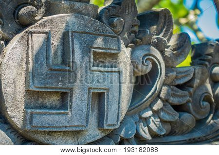 BALI, INDONESIA - MARCH 08, 2017: Nazi symbol carving over a wall concrete, that represent Hitler government, located in the city of Densapar in Bali Indonesia.