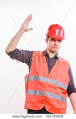 Job and work concept. Young male worker wearing safety vest and hard hat holding hand up. Repairman inspector at work.