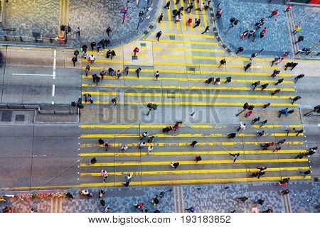people walking though road intersection in city from top view