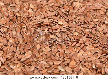 Background from scattered raw flax seeds close-up