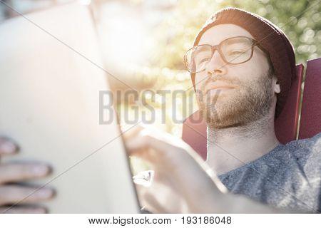 Hipster guy in park websurfing on digital tablet