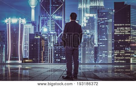 Rear view of indecisive businessman with blurred morden city skyline .