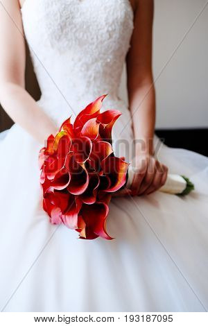 The bride is holding a wedding bouquet of red callas
