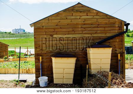 Green Recovery Of Rainwater And Small Wooden Cabin Outside In Town Garden