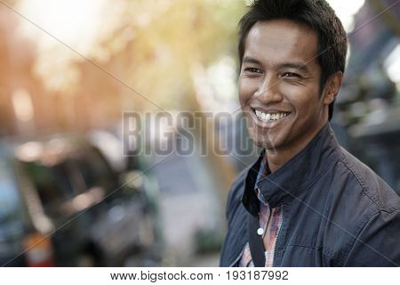 Smiling mixed-raced guy standing in the street