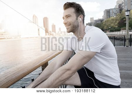 Jogger stretching out after running by East river