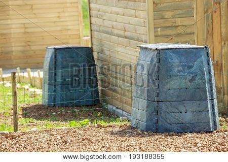 Black Plastic Compost Bin And Small Wooden Cabin In Town Garden