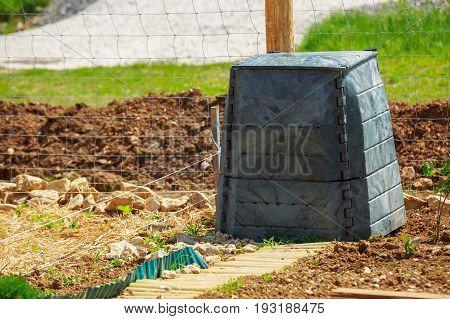 Black Plastic Compost Bin In Town Garden