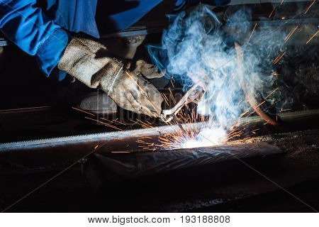 Industrial welder welding fabricated construction in factory Welding process by Shielded Metal Arc Welding (SMAW) or Stick Welding.