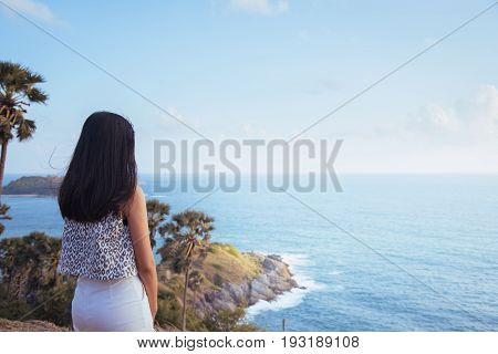 Asian women enjoy landscape view at Laem Phromthep Cape in sunset sky. The most famous tourist attraction in Phuket province Thailand.