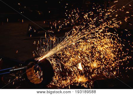 Worker cutting steel plate with acetylene welding cutting torch and bright sparks in steel construction industry.