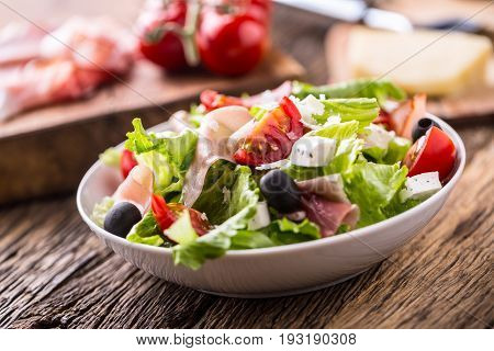 Salad. Fresh summer lettuce salad.Healthy mediterranean salad olives tomatoes parmesan cheese and prosciutto.