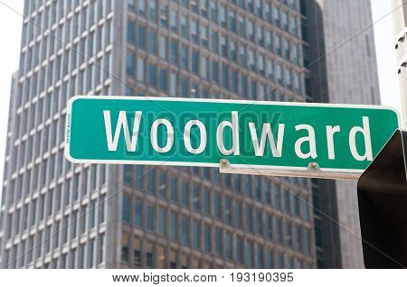 Street sign for Woodward Avenue, a main thoroughfare in the City of Detroit, Michigan. There is a generic office building in the background.