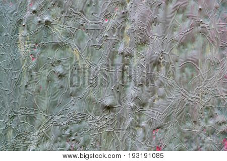 The texture of the walls of wood painted with red green grey brown yellow burgundy paint. Visible cracks bumps and depressions. Under the paint visible old layer of paint.