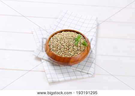 bowl of peeled brown lentils on checkered dishtowel