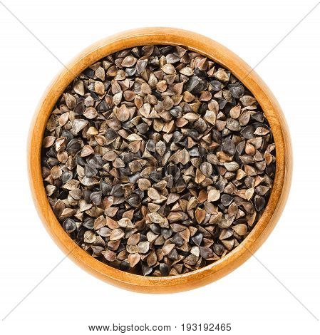 Common buckwheat seeds with hulls in wooden bowl. Fagopyrum esculentum, also Japanese or silverhull buckwheat. Gluten free pseudocereal. Dried seeds. Macro photo closeup from above on white background