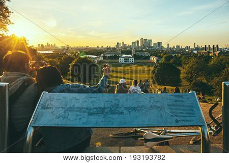 LONDON, UK - MAY 22, 2017: People sitting on the top of the hill at Greenwich Park, London, watching the sunset and taking photos. Every year millions of Londoners and tourists visit Greenwich Park.