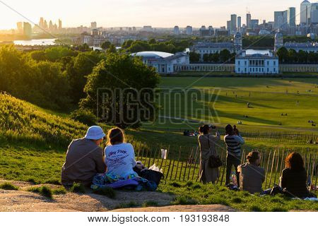 LONDON, UK - MAY 22, 2017: People sitting and standing on the top of the hill at Greenwich Park, London, watching the sunset and taking photos.