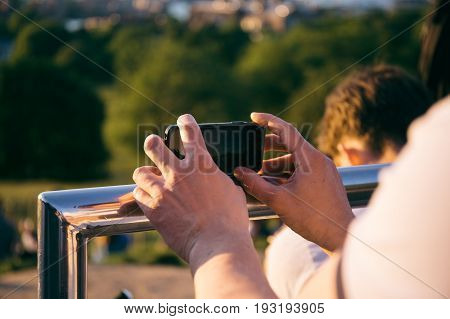Man holding a smartphone in hands, leaning on metal railing, stabilising to take a picture on the phone.