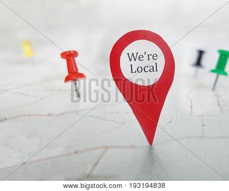 Red locator symbol with We're Local message on a map with tacks