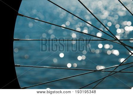 Bicycle wheel on the background of the sea. Bicycle wheel spokes