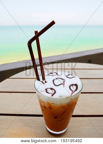 Iced mocha on wooden table with ocean background