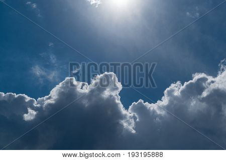 Blue sky with Cumulus clouds. Top the sun shines. The bright sun illuminates Cumulus clouds. The sky is clear and blue. A small haze.