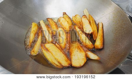 French fries potato snacks cooking with palm oil in stainless steel pan is scorch.