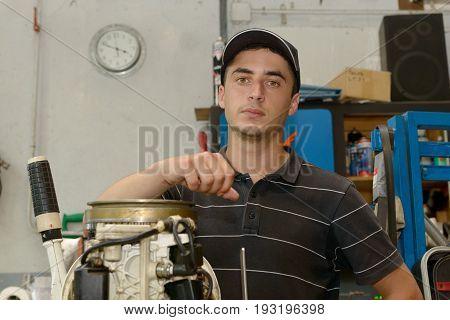 A young man mechanic repairing motor boat
