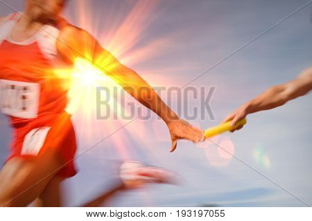Athletes passing relay baton