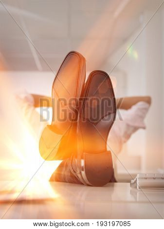 Businessman reclining with his feet up on desk in office