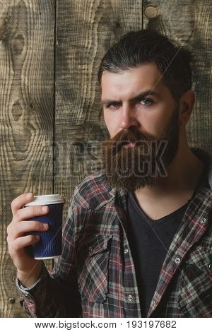 man or bearded caucasian hipster with grey hair long beard and moustache holding blue plastic cup on wooden background. Coffee to go. Healthy lifestyle and dieting