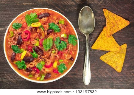 A photo of chilli con carne, a Mexican dish with red beans, coriander leaves, ground meat, and chilli peppers, on a dark rustic texture with nachos and a spoon, shot from above