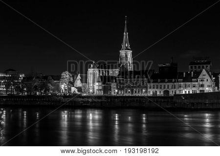 MAASTRICHT NETHERLANDS - JANUARY 16 2016: City in the night. Maas River in the foreground. Black and white. Maastricht is the oldest city of the Netherlands and the capital city of the province of Limburg.