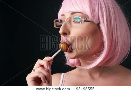 Portrait of glamour beauty Fashion Model Girl with Pink Hair and pink lips. Blue eyed Female model in stylish pink glasses suck lollipop. Colourful Hair. Colouring hair