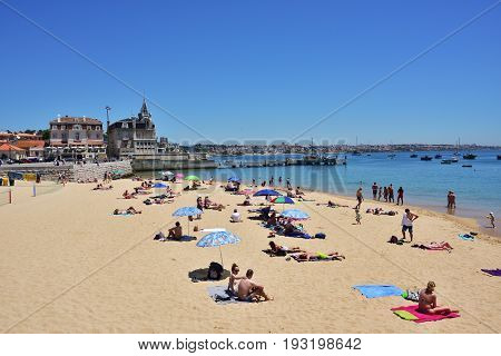 CASCAIS PORTUGAL - JUNE 13 2017: People sunbathing on the Praia Ribeira public beach. Cascais is famous and popular summer vacation spot for Portuguese and foreign tourists