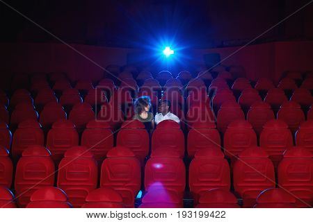 Young interracial couple sitting in an empty cinema hall watching a movie together copyspace love romance vip romantic anniversary date entertainment activity concept.