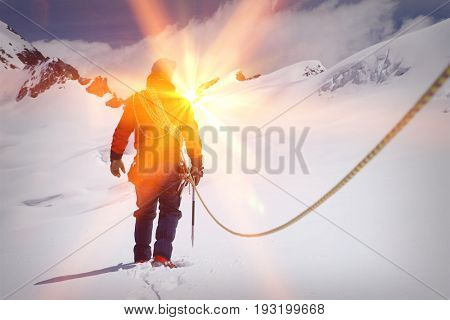 Rear view of a male hiker connected to safety line in snowy mountains