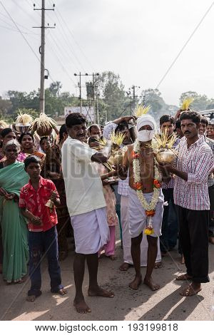 Mysore India - October 27 2013: The father of the bride fasted and didn't speak for five days. He is the central figure in a wedding procession. Yellow strings are palm tree seeds a symbol of fertility.
