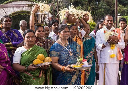 Mysore India - October 27 2013: Smiling white clothed groom is surrounded by group of women in colorful saris during wedding procession. Women carry fruit and palm seed strings as fertility symbols.
