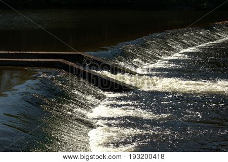 Water over a weir, salmon ladder in river