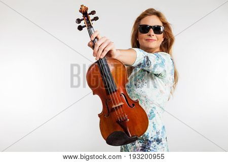 Young blond woman posing in studio with white background. sHe is a violinist